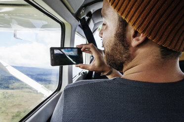 Rear view of man photographing landscape through smart phone from airplane window - CAVF37969