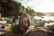 Rear view of male hiker sitting on rocky lakeshore during sunset - CAVF37975