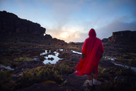 Rear view of hiker in raincoat walking on rock against cloudy sky - CAVF37984