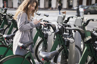 Young woman text messaging through smart phone by bike shares at parking lot - CAVF38005