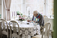 Senior man writing in book at dining table in nursing home - MASF03260