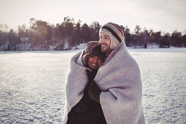 Smiling couple wrapped in blanket while standing on field during winter - MASF03263