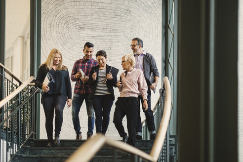Team of creative business people moving downstairs at office - MASF03275