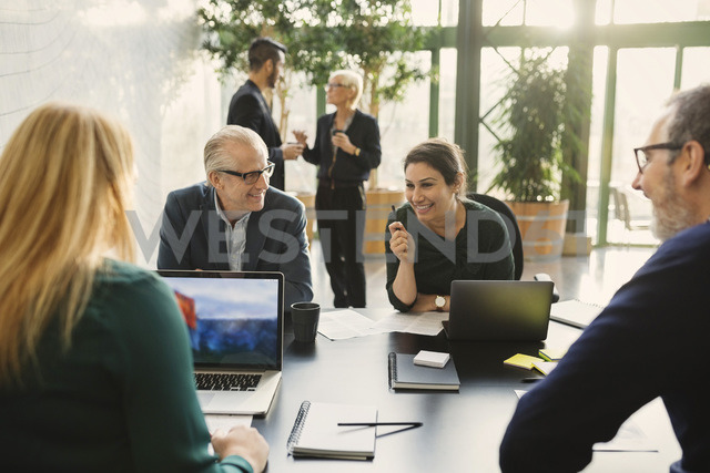Smiling businesswoman discussing with colleagues in creative office - MASF03281