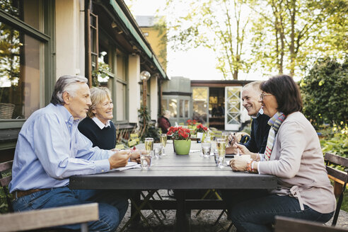 Side view of happy senior couples having food at outdoor restaurant - MASF03311