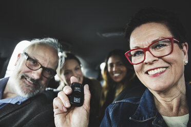 Smiling senior woman holding remote while sitting with people in car - MASF03314