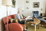 Senior woman analyzing document while using laptop at home - MASF03323