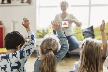 Rear view of students raising hands while teacher showing digital tablet at preschool - MASF03347