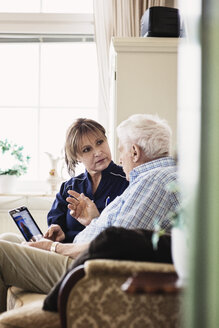 Senior man talking to caretaker while using digital tablet at nursing home - MASF03350