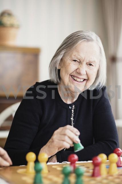 Portrait of happy senior woman playing Ludo in nursing home - MASF03353