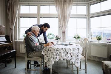 Senior man using laptop with caretaker at nursing home - MASF03356
