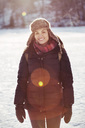 Portrait of smiling woman standing on snow covered field - MASF03359