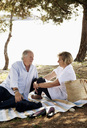 Senior man and mature woman enjoying picnic together - MASF03365