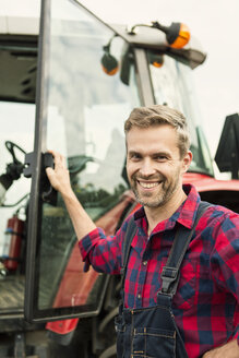 Portrait of smiling man standing by tractor at farm - MASF03380