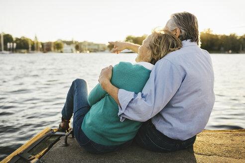 Senior man showing something to woman while sitting on pier - MASF03401