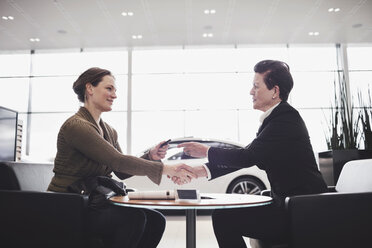 Saleswoman and customer shaking hands while talking at desk in showroom - MASF03407