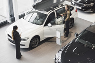 Saleswoman looking at customer examining car in showroom - MASF03410