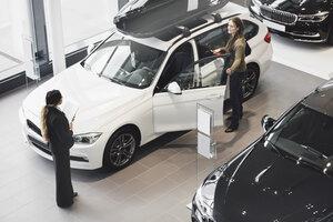 Saleswoman looking at customer examining car in showroom - MASF03410