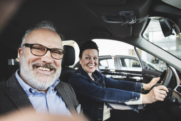 Portrait of happy senior man and woman sitting in car at showroom - MASF03413