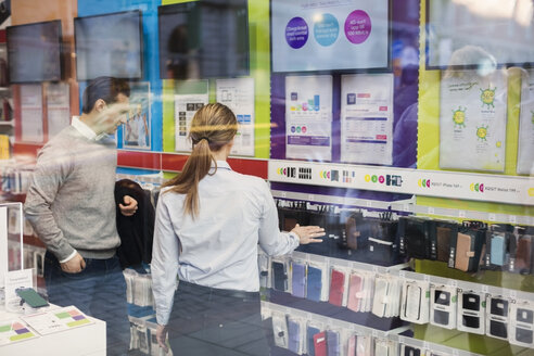 Saleswoman helping customer in buying phone cover seen through glass - MASF03419