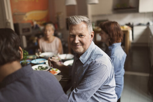 Portrait of happy mature man sitting with friends at table - MASF03425