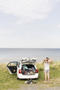 Rear view of woman stretching by car on field against sea - MASF03428