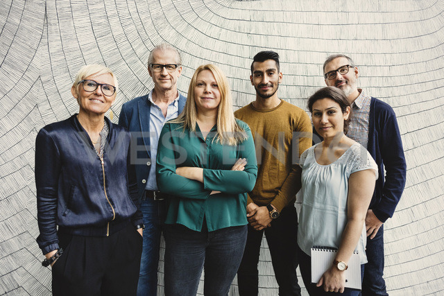 Portrait of confident multi-ethnic business people standing against wall in office - MASF03467