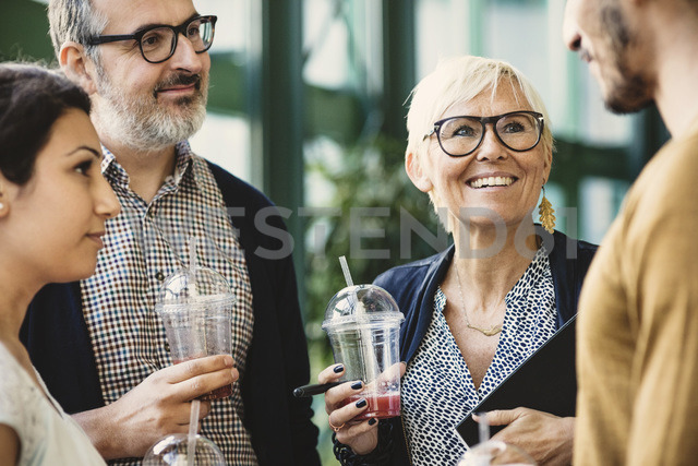 Multi-ethnic business people discussing while having refreshments in creative office - MASF03470