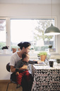 Mother carrying baby girl looking in laptop while sitting at kitchen - MASF03476
