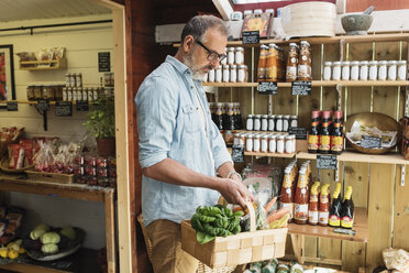 Mature man carrying basket while shopping in food store - MASF03488
