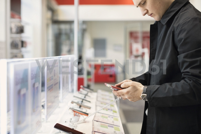 Midsection of young man using smart phone at store - MASF03497