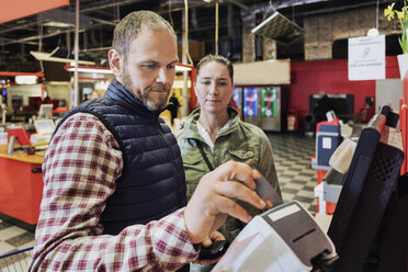 Male customer doing payment while standing with woman at grocery store - MASF03506