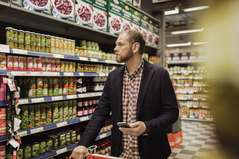 Male customer holding smart phone while shopping in grocery store - MASF03509