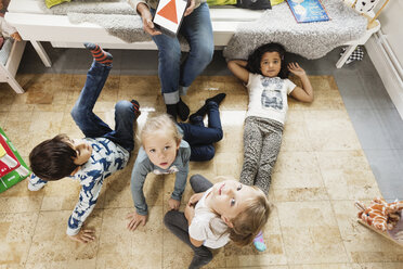 High angle view of children resting while teacher showing triangle on digital tablet - MASF03512