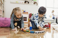 Little boy and girl playing with toy train at preschool - MASF03515