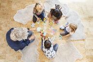 High angle view of teacher and children playing jigsaw puzzle - MASF03518