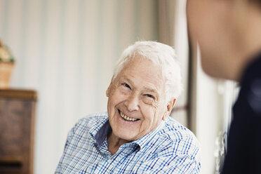 Happy senior man looking at caretaker in nursing home - MASF03521