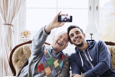 Happy senior man taking selfie with caretaker through smart phone at nursing home - MASF03524