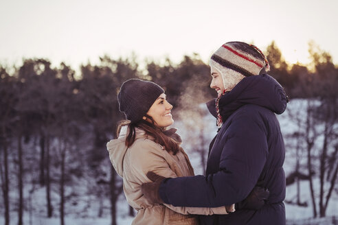 Happy couple embracing on field during winter - MASF03530