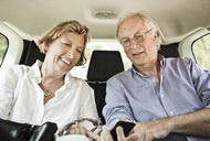 Happy couple looking in mobile phone while sitting in car - MASF03536