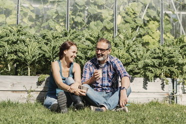 Happy farmers enjoying coffee break while sitting on grass against greenhouse - MASF03554