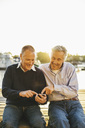 Happy senior male friends using mobile phone on pier - MASF03560