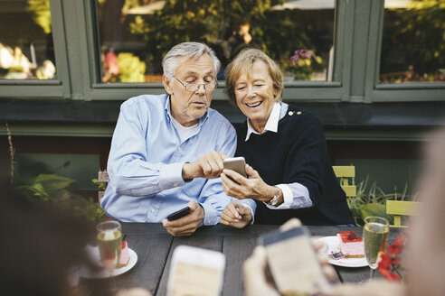 Happy senior couple using mobile phone at outdoor restaurant - MASF03569