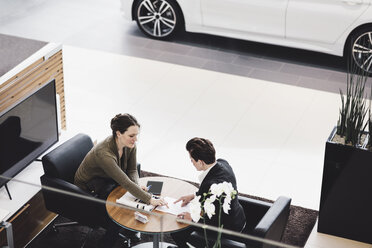 High angle view of salesperson explaining paperwork to customer at showroom - MASF03572