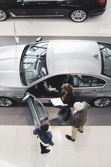 High angle view of saleswoman showing car to customers at showroom - MASF03575