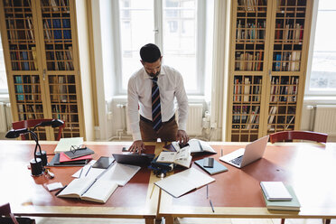 High angle view of professional researching while standing at table in law library - MASF03590