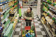 High angle view of thoughtful woman leaning on shopping cart at supermarket - MASF03596