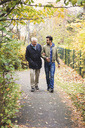 Full length of happy senior man with caretaker walking in park - MASF03602