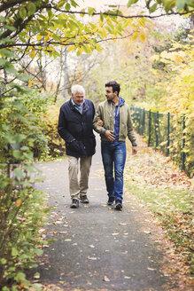 Full length of happy senior man with caretaker walking in park - MASF03602