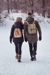 Full length rear view of couple walking on snow covered field - MASF03605